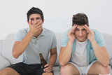 Disappointed soccer fans watching tv