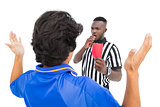 Referee showing red card to football player