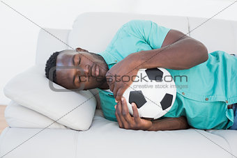 Football fan hugging ball on couch