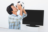 Football fan kissing ball against tv