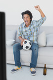 Soccer fan cheering while watching tv