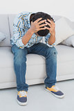 Tensed football fan sitting on couch