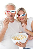 Mature couple wearing 3d glasses eating popcorn