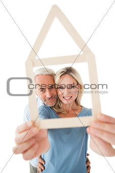 Mature couple looking through house outline