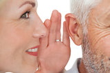 Woman whispering secret into a man's ear