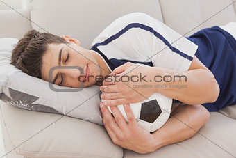 Football fan sleeping with ball