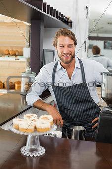 Handsome barista smiling at camera