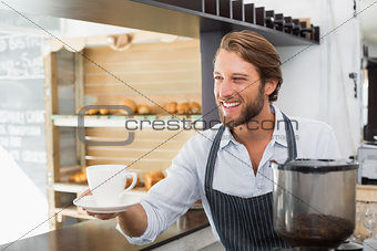 Handsome barista offering a cup of coffee