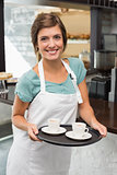 Pretty barista smiling at camera holding tray