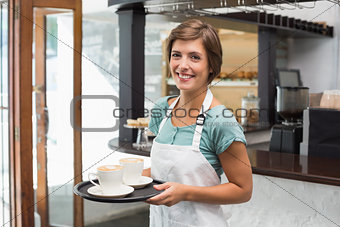 Pretty barista smiling at camera holding tray