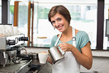 Pretty barista pouring milk into cup of coffee