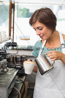 Pretty barista pouring milk into cup of coffee