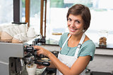 Pretty barista making coffee smiling at camera