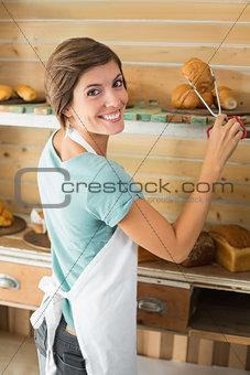 Pretty waitress picking up croissant
