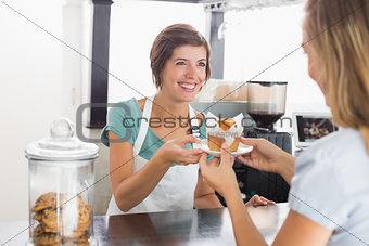 Pretty waitress serving muffin to customer