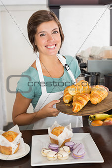 Pretty waitress showing tray of croissants