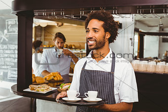 Handsome waiter smiling and holding tray