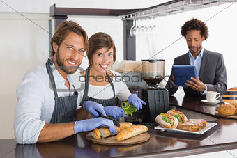 Happy servers preparing sandwiches together