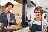 Happy server preparing food at counter