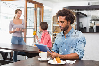 Handsome man using tablet while having coffee
