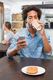 Handsome man sending a text drinking coffee