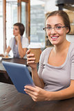 Pretty blonde enjoying a coffee using tablet pc