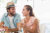 Happy couple enjoying coffee and cake