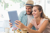 Happy couple enjoying coffee using tablet