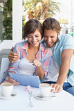 Happy couple on a date using tablet pc