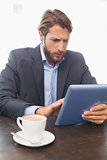 Businessman working on his tablet having coffee