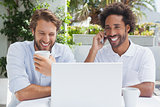 Happy friends enjoying coffee together with laptop