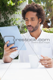 Thoughtful man having a coffee using tablet