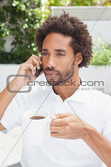 Smiling man on the phone having coffee