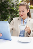 Beautiful businesswoman having a coffee using tablet