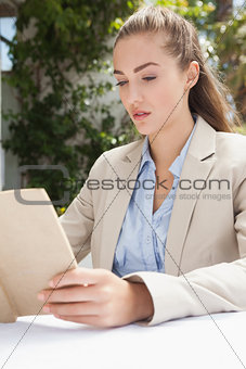 Beautiful businesswoman reading a book
