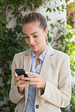 Beautiful businesswoman texting on phone