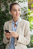 Beautiful businesswoman texting on phone