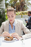 Businesswoman having sandwich for lunch