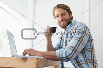 Casual man using laptop drinking espresso