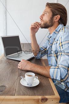 Casual man using laptop having coffee