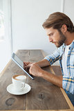 Casual man having a coffee using tablet
