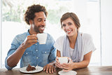 Casual couple having coffee and cake together