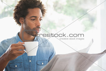 Casual man having coffee while reading newspaper