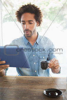 Casual man having coffee while using tablet