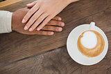 Couple holding hands beside cappuccino