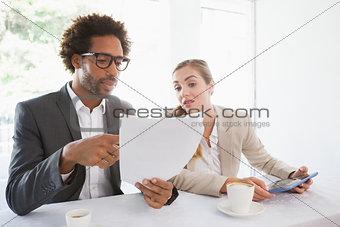 Business people having coffee looking at file