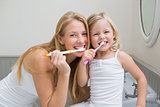 Happy mother and daughter brushing their teeth