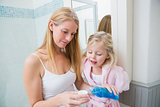 Happy woman pouring blue mouthwash with daughter