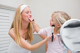 Happy mother and daughter playing with make up