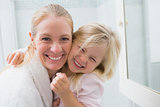 Happy mother and daughter smiling at camera
